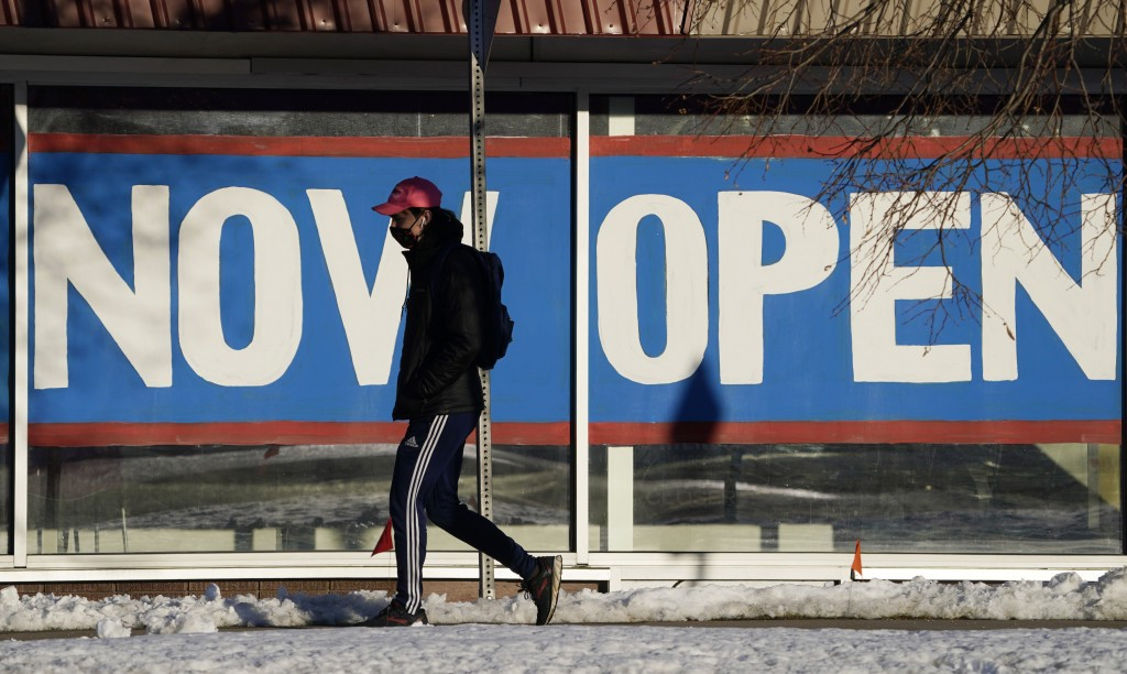 A pedestrian in a face covering walks past the sign plastered on the windows of a restaurant to announce that it is open after closure because of the ...