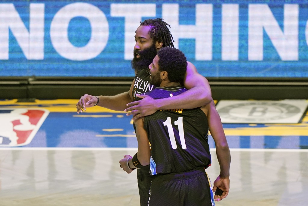 Brooklyn Nets guard James Harden (13) embraces guard Kyrie Irving (11) after Irving scored on a play during the second quarter of an NBA basketball ga...