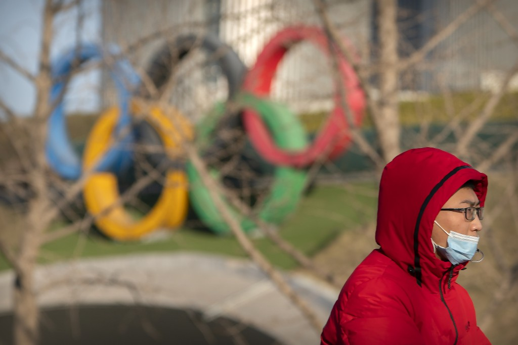 A man wearing a face mask to protect against the spread of the coronavirus rides a bicycle pas the Olympic rings at the base of the Olympic Tower in B...