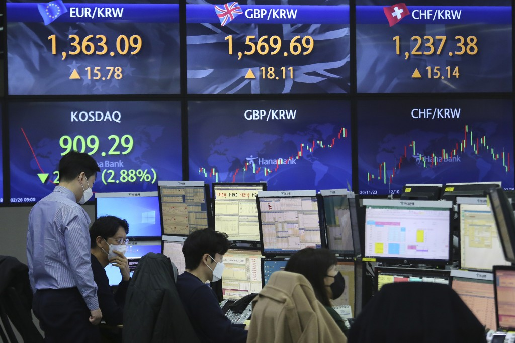 Currency traders watches monitors at the foreign exchange dealing room of the KEB Hana Bank headquarters in Seoul, South Korea, Friday, Feb. 26, 2021....