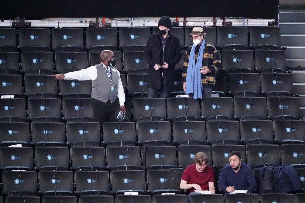 An usher talks to fans before an NBA basketball game between the Brooklyn Nets and the Orlando Magic, Thursday, Feb. 25, 2021, in New York. (AP Photo/...