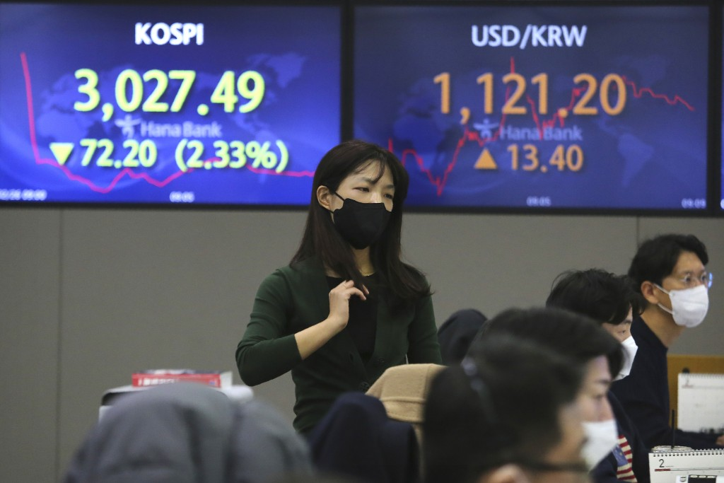 A currency trader walks near screens showing the Korea Composite Stock Price Index (KOSPI), left, and the foreign exchange rate between U.S. dollar an...