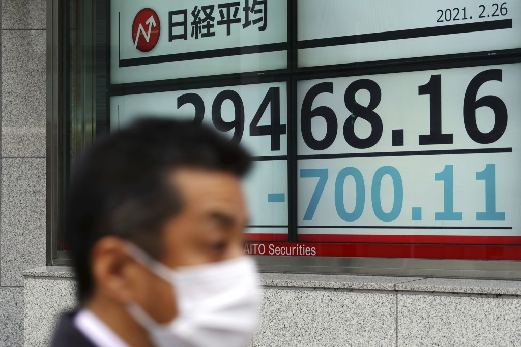 A man wearing a protective mask walks in front of an electronic stock board showing Japan's Nikkei 225 index at a securities firm Friday, Feb. 26, 202...