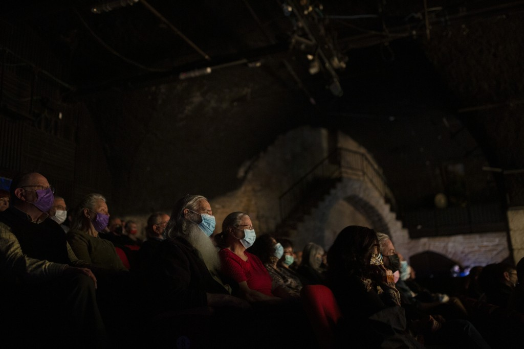 The audience wearing protective face masks watches on opening night at the Khan Theater during a performance where all guests were required to show pr...