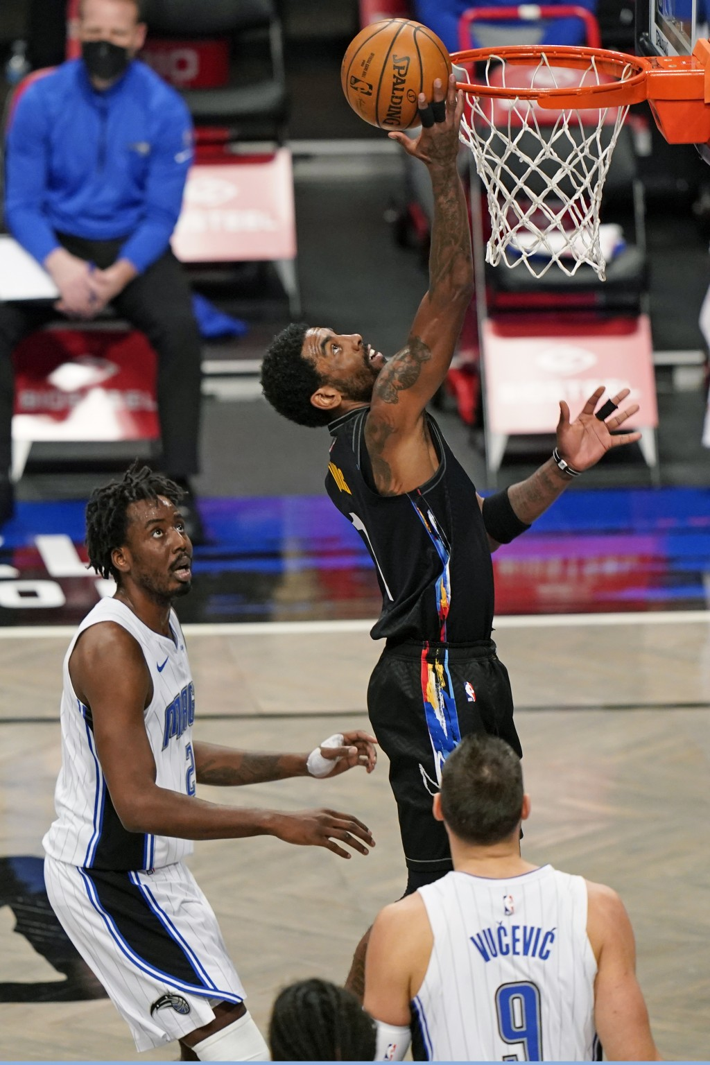 Brooklyn Nets guard Kyrie Irving (11) tries to tip the ball in as Orlando Magic forward Al-Farouq Aminu (2) and center Nikola Vucevic (9) look on duri...
