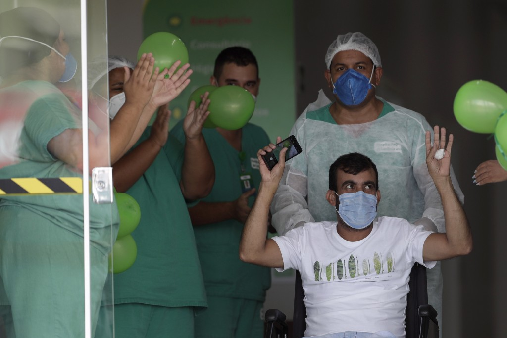 COVID-19 patient Wellington Bernardo dos Santos, 46, thanks health workers after being discharged from the Luziania field hospital, a suburb of Brasil...