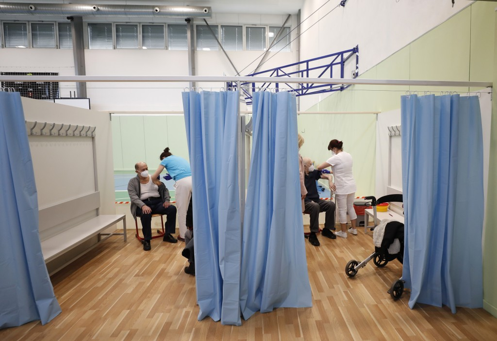 Elderly men receive Moderna COVID-19 vaccine at a sports hall in Ricany, Czech Republic, Friday, Feb. 26, 2021. With new infections soaring due to a h...