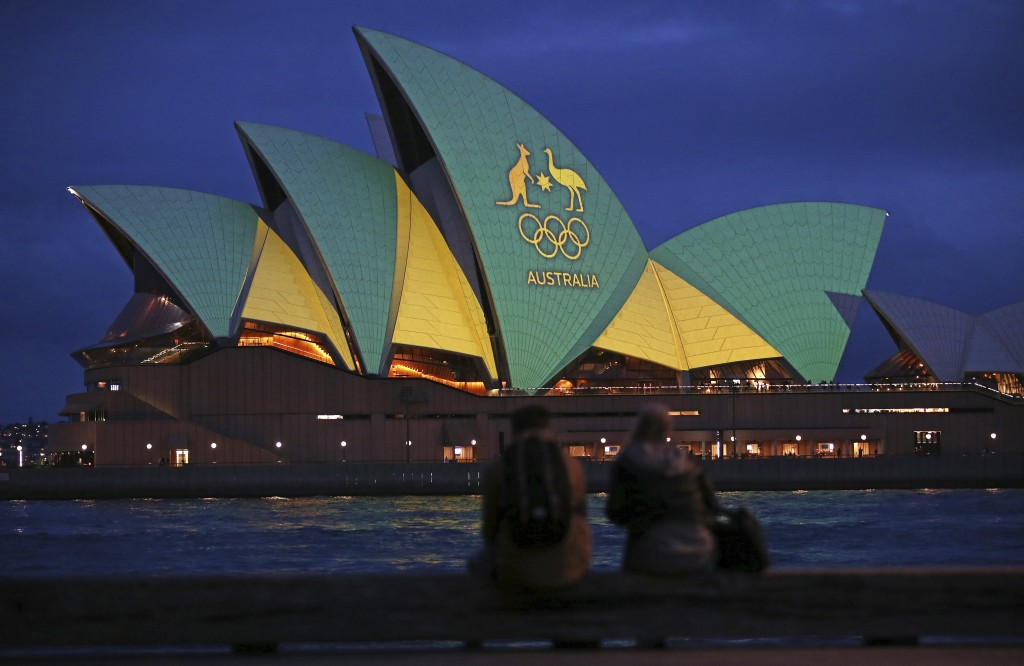 FILE - In this Friday, Aug. 5, 2016, file photo, a couple sit on a dock to look at the sails of the Sydney Opera House that are illuminated with the g...
