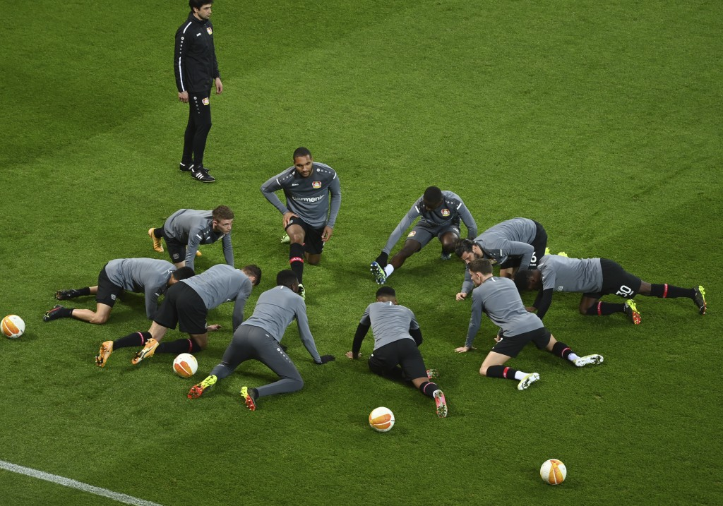 Bayer Leverkusen players stretch during a warm up before the Europa League round of 32, 2nd leg soccer match between Bayer 04 Leverkusen and Young Boy...