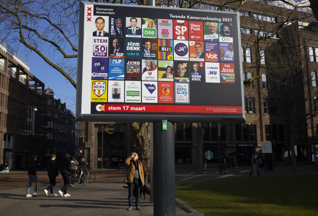 A man shields his eyes from the sun as he looks up at an election billboard with a multitude of political parties in Amsterdam, Netherlands, Saturday,...