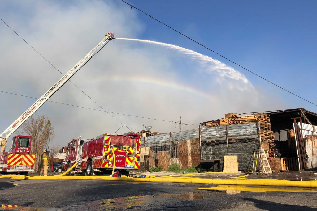 Firefighters from the Downey Fire Department battle a fire at at commercial yard in Compton, Calif., on Friday, Feb. 26, 2021. A huge fire visible acr...