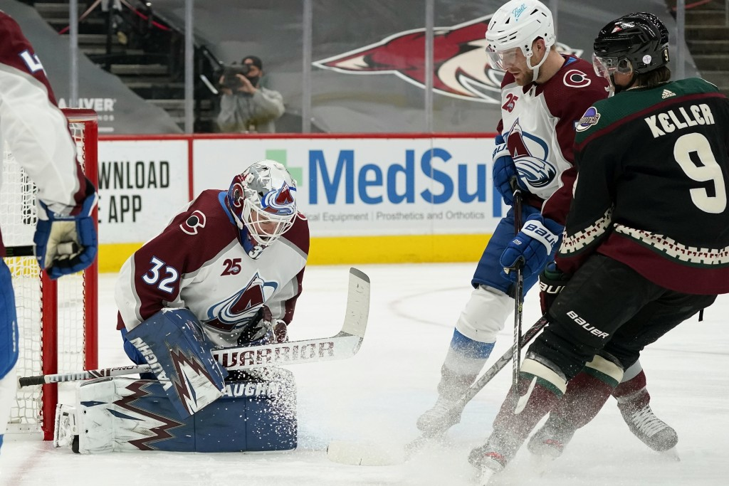 Colorado Avalanche goaltender Hunter Miska (32) makes a save as Arizona Coyotes right wing Clayton Keller (9) and Avalanche defenseman Devon Toews, se...