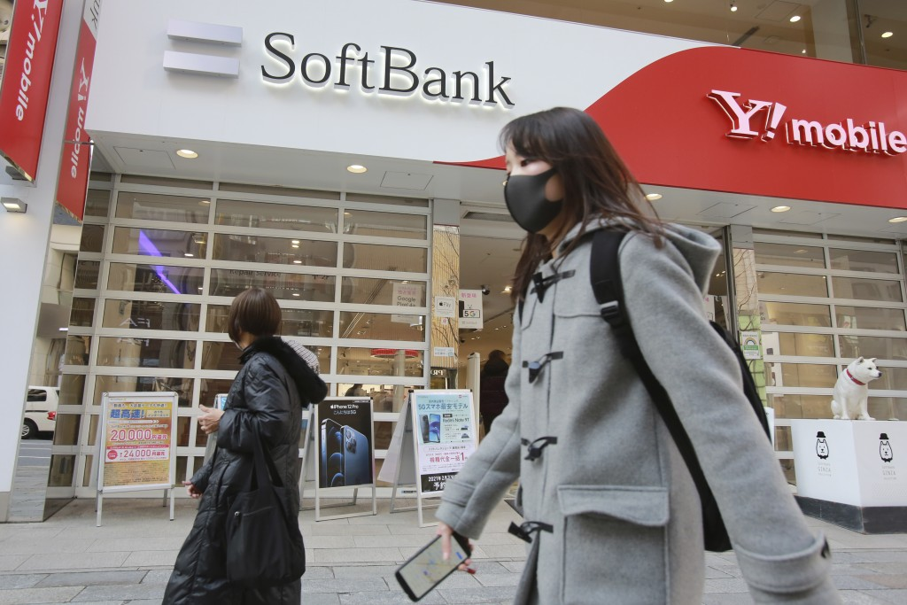 People walk by a SoftBank shop in Tokyo, Monday, Feb. 8, 2021. Japanese telecommunications and technology conglomerate Softbank Group Corp. reported M...