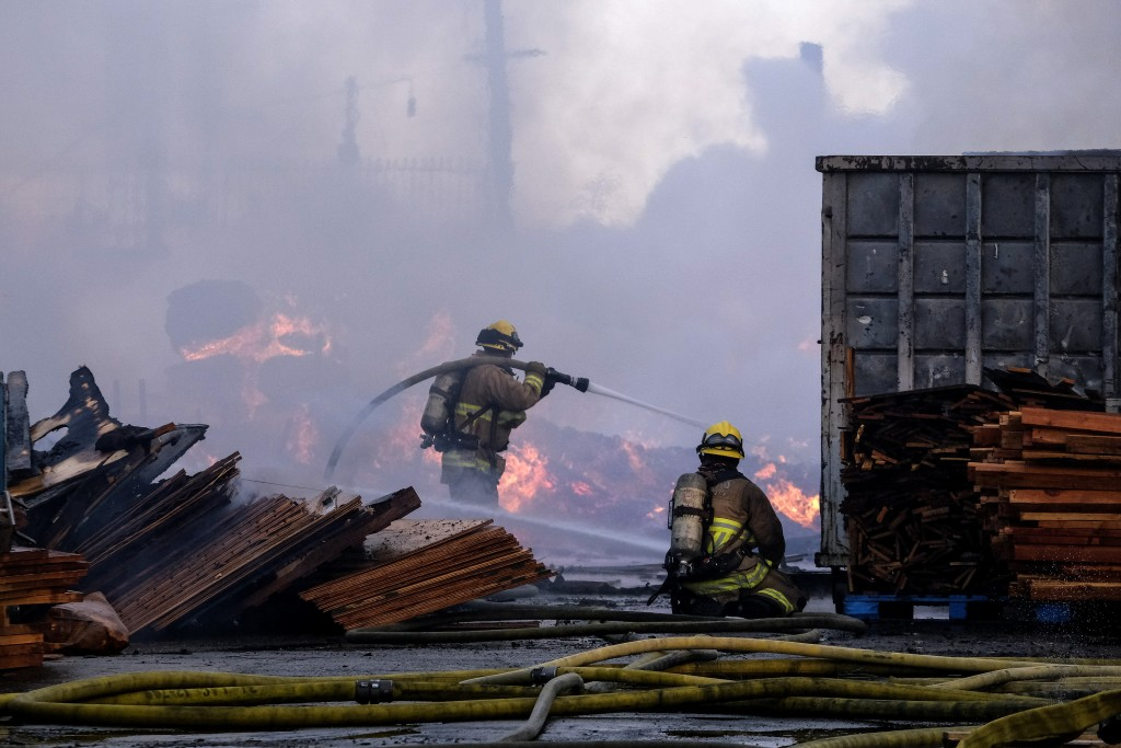 Firefighters battle a fire at a commercial yard in Compton, Calif., on Friday, Feb. 26, 2021. A huge fire visible across Los Angeles burned material i...