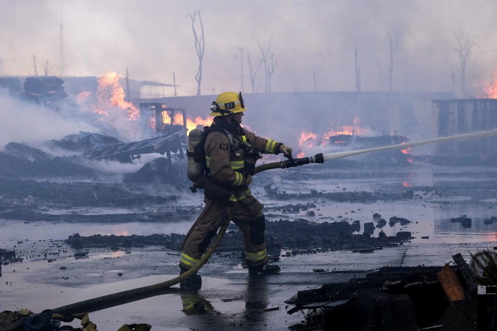 A firefighter battles a fire at a commercial yard in Compton, Calif., on Friday, Feb. 26, 2021. A huge fire visible across Los Angeles burned material...