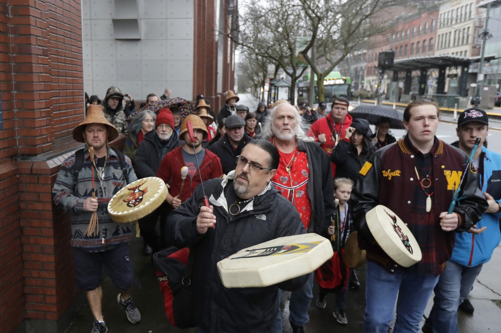 FILE - In this Jan. 6, 2020, file photo, Tony A. (Naschio) Johnson, center, elected chairman of the Chinook Indian Nation, plays a drum as he leads tr...