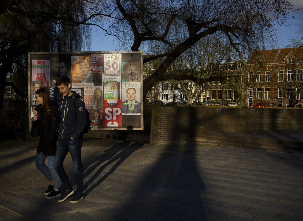 Two people pass election posters in Den Bosch, Netherlands, Friday, Feb. 26, 2021. After more than a decade in power, a recent scandal that forced him...