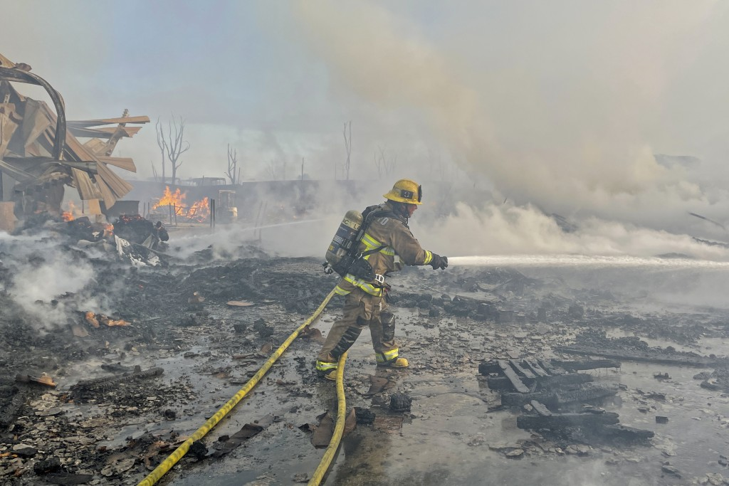 A firefighter battles a fire at at commercial yard in Compton, Calif., on Friday, Feb. 26, 2021. A huge fire visible across Los Angeles burned materia...