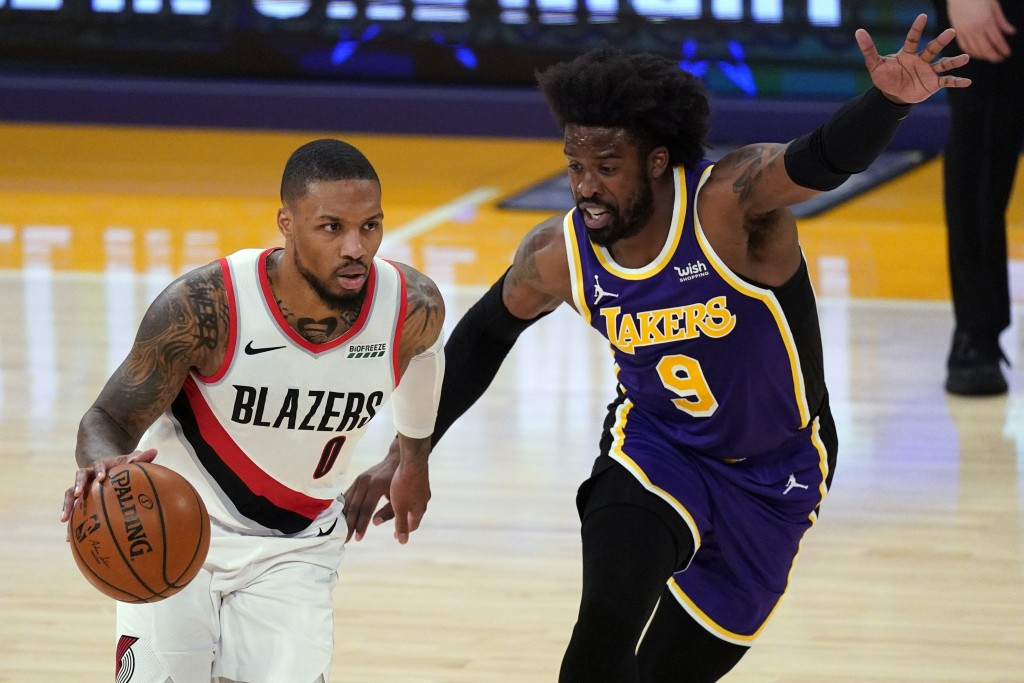 Los Angeles Lakers guard Wesley Matthews (9) defends against Portland Trail Blazers guard Damian Lillard (0) during the first half of an NBA basketbal...