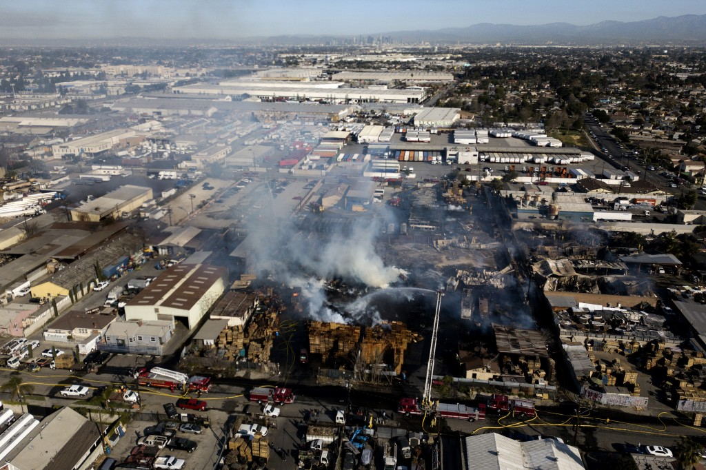 In this photo taken by a drone, firefighters battle a fire at a commercial yard in Compton, Calif., on Friday, Feb. 26, 2021. A huge fire visible acro...