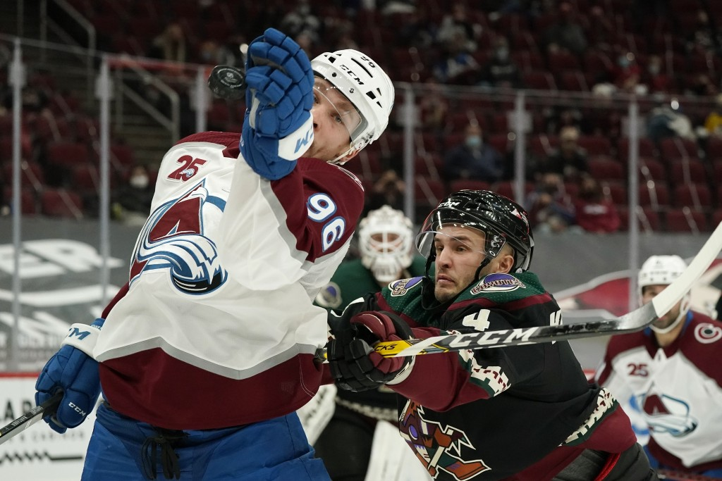 Colorado Avalanche right wing Mikko Rantanen (96) tries to control the puck in the air as he gets hit by Arizona Coyotes defenseman Niklas Hjalmarsson...