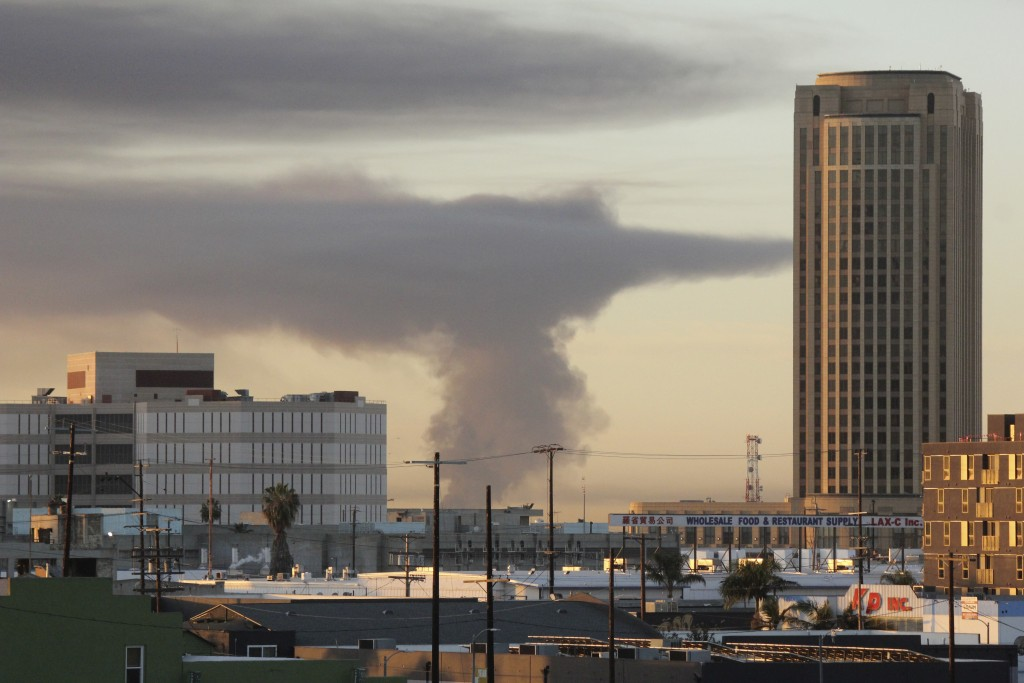 In this view from Los Angeles, smoke rises in the distance from a fire at at commercial yard in Compton, Calif., Friday, Feb. 26, 2021. A huge fire vi...