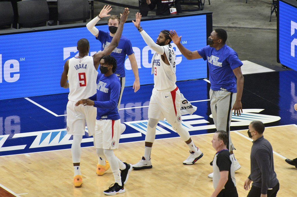 Los Angeles Clippers center Serge Ibaka (9) high-fives teammates after scoring a basket at the end of the first half of the team's NBA basketball game...