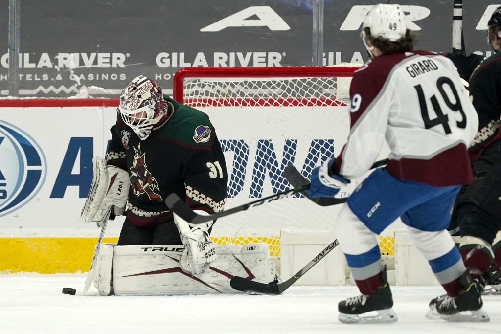Arizona Coyotes goaltender Adin Hill (31) makes a save on a shot as Colorado Avalanche defenseman Samuel Girard (49) looks for a rebound during the fi...
