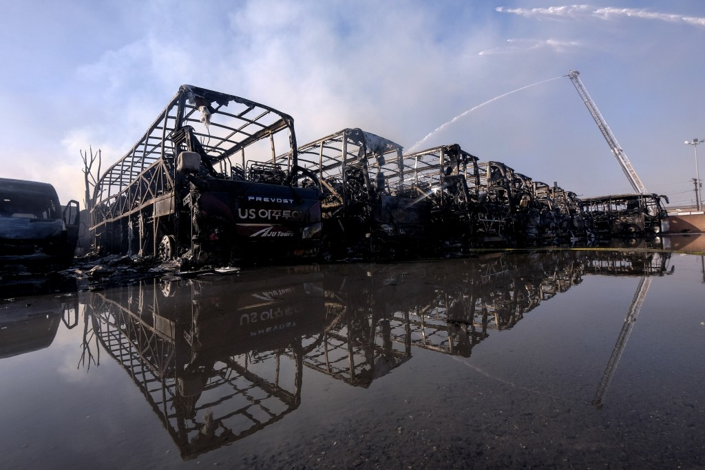 Firefighters stray water on the burned buses at a commercial yard in Compton, Calif., on Friday, Feb. 26, 2021. A huge fire visible across Los Angeles...