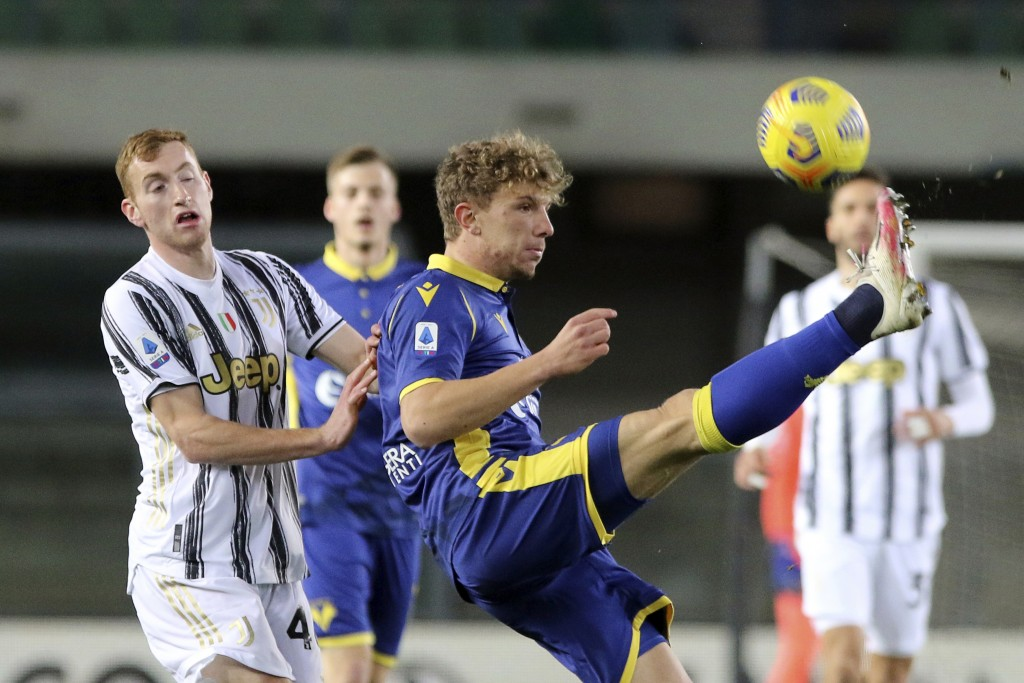 Verona's Matteo Lovato, right, and Juventus' Dejan Kulusevski battle for the ball during the Italian Serie A soccer match between Verona and Juventus ...