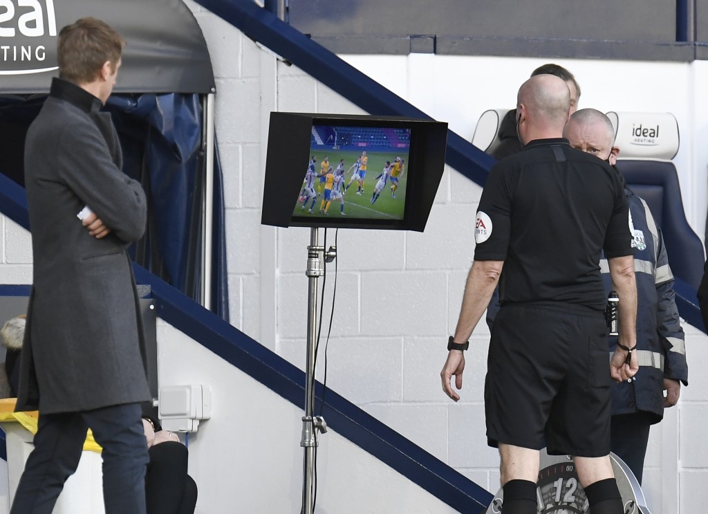 Referee Lee Mason, right, and Brighton's head coach Graham Potter watching the VAR monitor during the English Premier League soccer match between West...