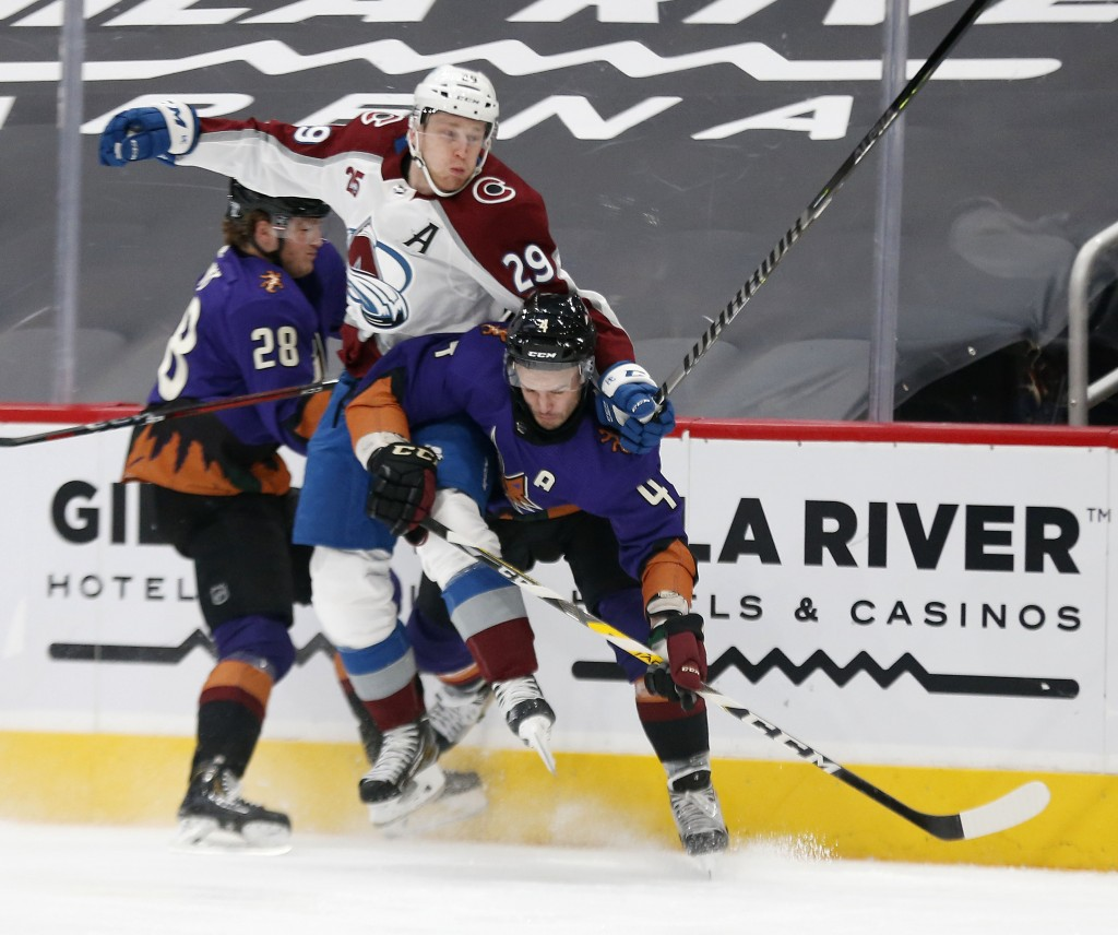 Colorado Avalanche's Nathan MacKinnon gets sandwiched between Arizona Coyotes' Dryden Hunt, right, and Niklas Hjalmarsson during the first period of a...