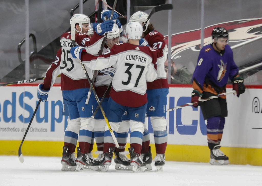 Colorado Avalanche's Andre Burakovsky (95), J.T. Compher (37) and Ryan Graves (27) mob Jacob MacDonald, center, after a goal against the Arizona Coyot...
