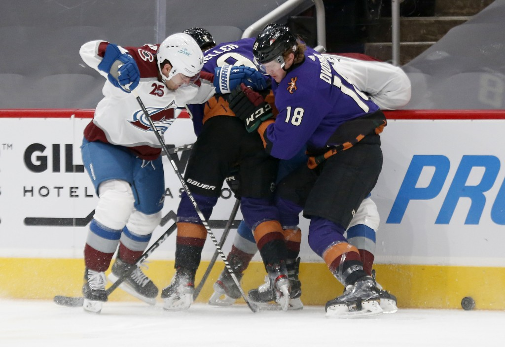 Colorado Avalanche's Logan O'Connor, left, battles with Arizona Coyotes' Clayton Keller, middle, and Christian Dvorak during the first period of an NH...