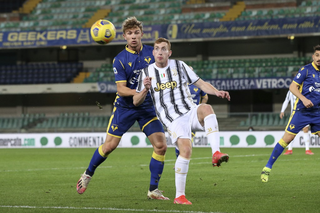 Matteo Lovato, left, and Dejan Kulusevski compete for the ball during the Italian Serie A soccer match between Verona and Juventus at the Bentegodi st...