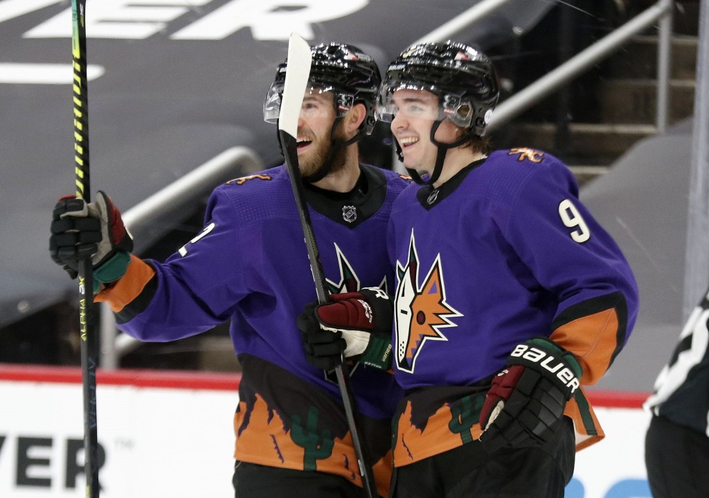 Arizona Coyotes' Jordan Oesterle (82) celebrates with Clayton Keller (9) after he scored against the Colorado Avalanche during the second period of an...