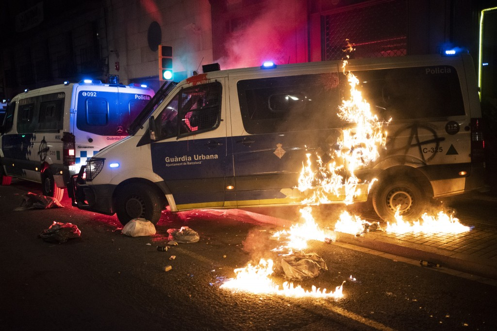 A police van is set on fire as protestors throw molotov cocktails at police during clashes following a protest condemning the arrest of rap singer Pab...