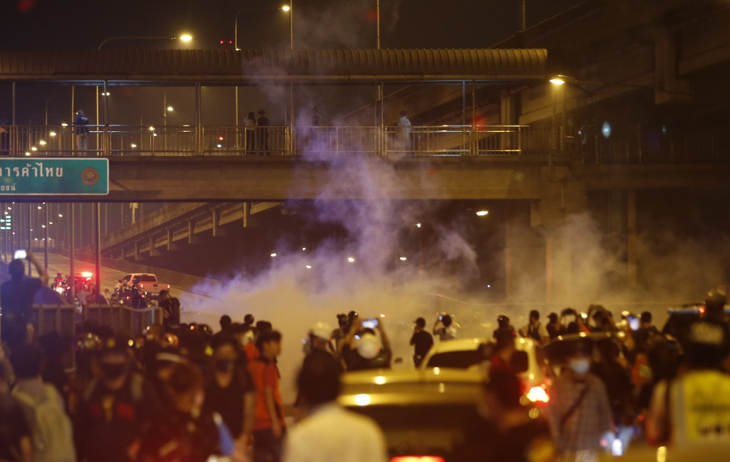 Riot policemen shoot tear gas on the road near to anti-government protesters, during a protest in Bangkok, Thailand, Sunday, Feb. 28, 2021. The anti-g...