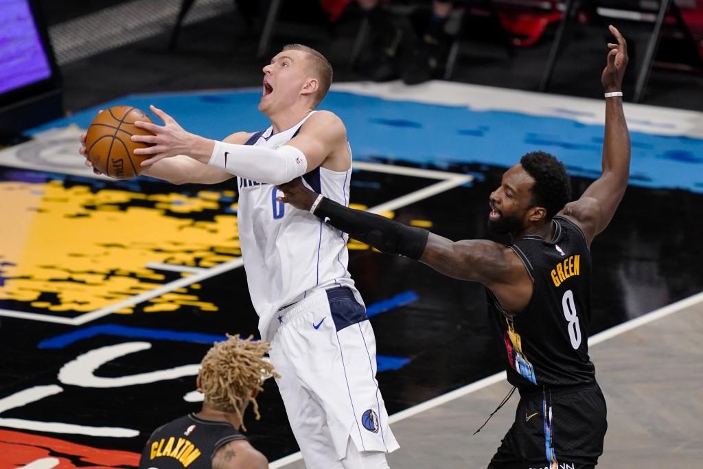 Dallas Mavericks center Kristaps Porzingis (6) shoots against Brooklyn Nets forward Jeff Green (8) during the second half of an NBA basketball game Sa...