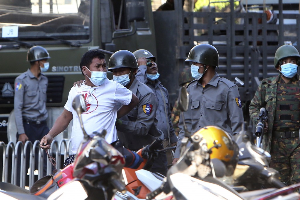 A man is held by police during a crackdown on anti-coup protesters holding a rally in front of the Myanmar Economic Bank in Mandalay, Myanmar, Monday,...