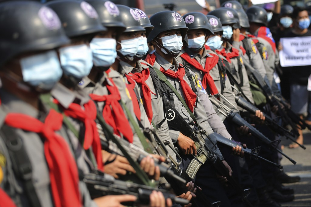Armed riot police are seen near protesters in Naypyitaw, Myanmar, Monday, Feb. 8, 2021. In the month since Feb. 1 coup, the mass protests occurring ea...