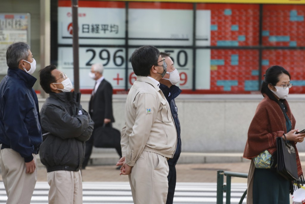 People stand by an electronic stock board of a securities firm in Tokyo, Monday, March 1, 2021. Asian shares were higher on Monday on hopes for Presid...
