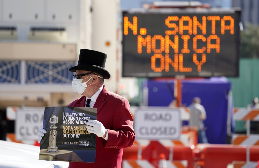 Gregg Donovan demonstrates with a sign protesting the lack of Black members in the Hollywood Foreign Press Association, outside a road closure near th...