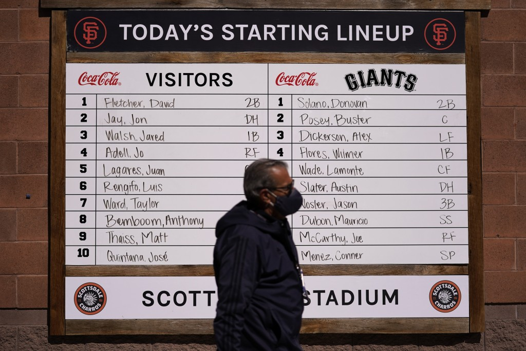 A man with a face mask walks past a lineup board before a spring baseball between the San Francisco Giants and the Los Angeles Angels in Scottsdale , ...