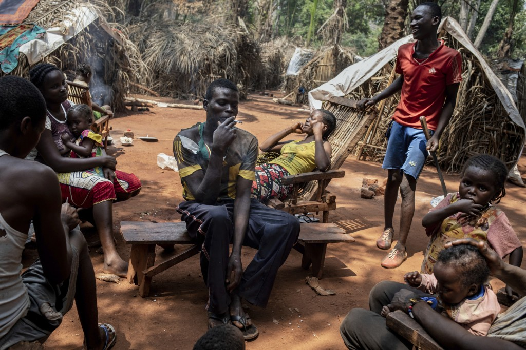 """Saint-Cyr Boussa smokes a cigarette, surrounded by his brothers in the village of Cesacoba, Central African Republic, Sunday Feb. 14, 2021. """"We ran aw..."""