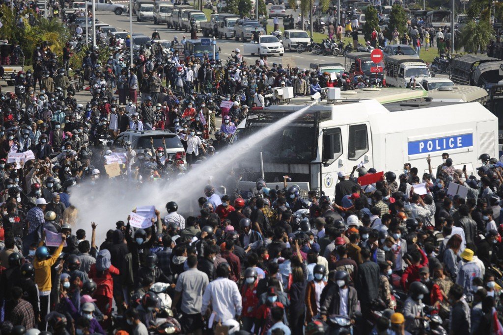 A police truck sprays water to a crowd of protesters in Naypyitaw, Myanmar, Monday, Feb. 8, 2021. In the month since Feb. 1 coup, the mass protests oc...