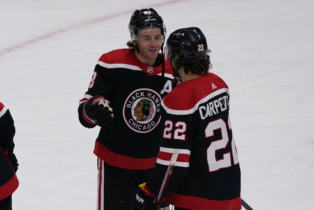Chicago Blackhawks' Patrick Kane, left, celebrates his 400th career goal with Ryan Carpenter after they defeated the Detroit Red Wings in an NHL hocke...