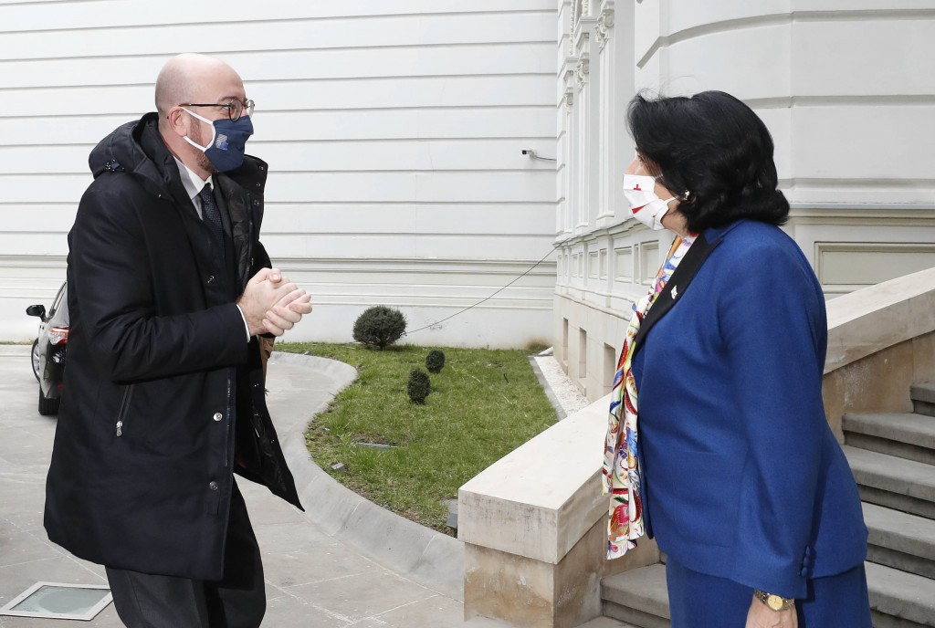 In this photo provided by the Georgian Presidential Press Office, Georgia's President Salome Zurabishvili, right, greets European Council President Ch...