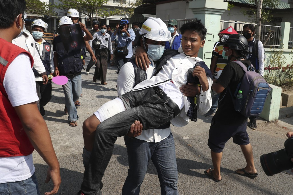 A protester wounded during a protest against a military coup is carried by his colleague in Mandalay, Myanmar, Sunday, Feb. 28, 2021. In the month sin...