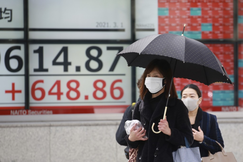 People walk by an electronic stock board of a securities firm in Tokyo, Monday, March 1, 2021. Asian shares were higher on Monday on hopes for Preside...